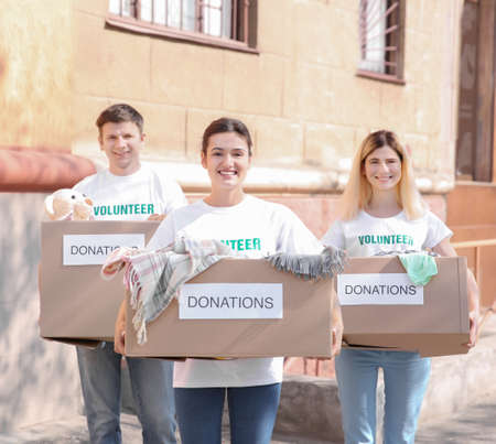 Volunteers with boxes outdoors. Poverty concept