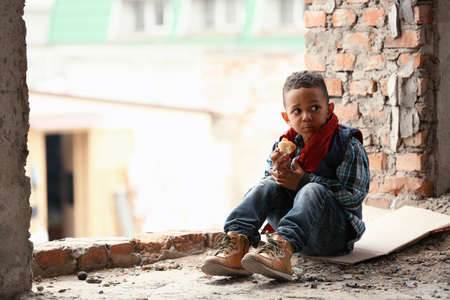 Cute little boy sitting on floor with piece of bread in abandoned building. Poverty concept