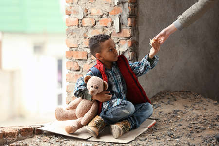 Woman giving piece of bread to cute little boy in abandoned building. Poverty concept