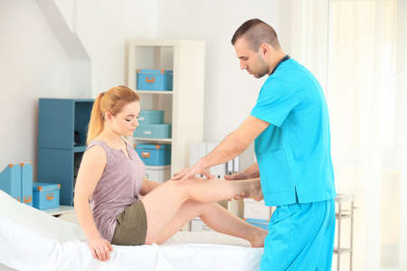 Male orthopedist with patient in his office Stock Photo