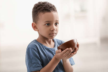 Cute little boy with bowl on blurred background. Poverty concept