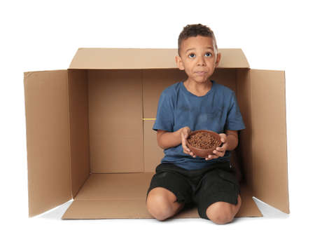 Cute little boy living in box on white background. Poverty concept Stock Photo