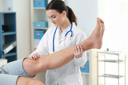 Orthopedist examining patient in clinic� Stock Photo