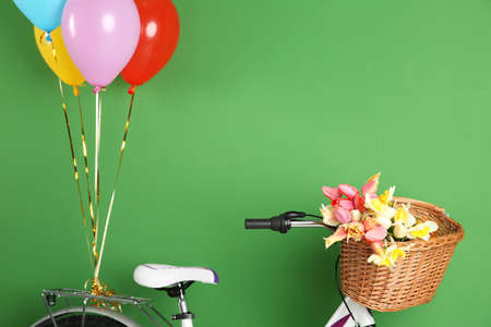 Bicycle with basket of flowers and balloons on color background