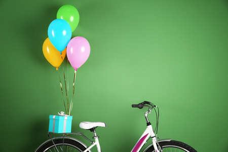 Bicycle with air balloons and gift box on color background