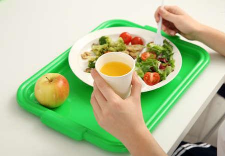 Schuljunge, der bei Tisch köstliches Essen% 00 isst Standard-Bild