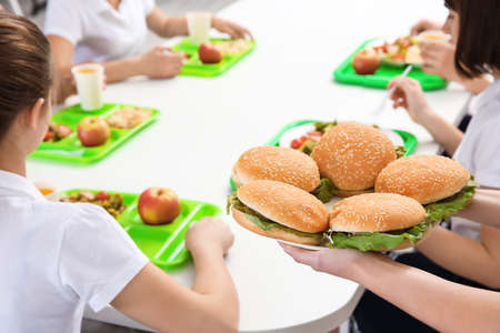 Woman serving plate with delicious sandwiches to children at school canteen