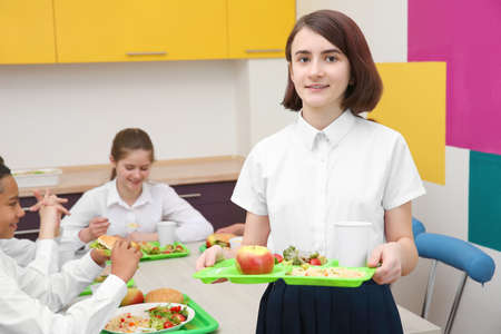 Cute girl holding tray with delicious food in school canteen Banque d'images