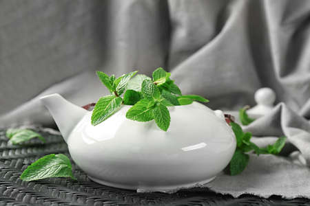 Teapot with fresh lemon balm leaves on table Stock fotó - 97801975