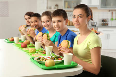 Children eating delicious sandwiches in school canteen