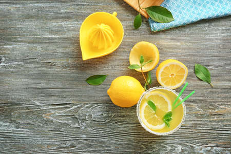Composition of lemon juice and fresh fruit on wooden background