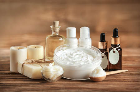 Composition of Shea butter with cosmetic products on wooden table