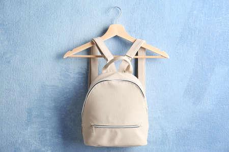 Leather backpack on hanger against light background