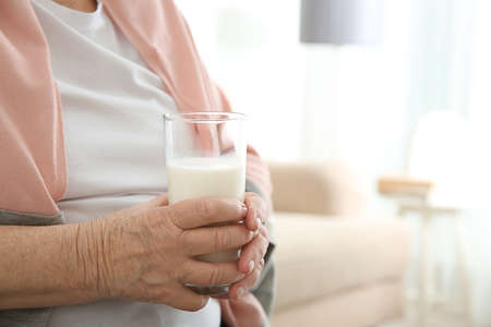 Old woman holding glass with fresh milk, closeup Stock Photo