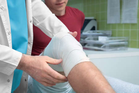 Orthopedist applying bandage onto patients leg in clinic