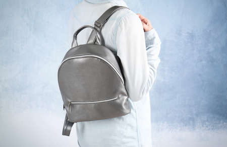 Young woman with leather backpack on light background