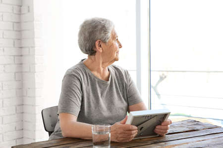 Elderly woman holding wooden frame and looking out the window. Concept of retirement