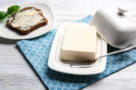 Piece of butter in dish and toast on light table Stock Photo