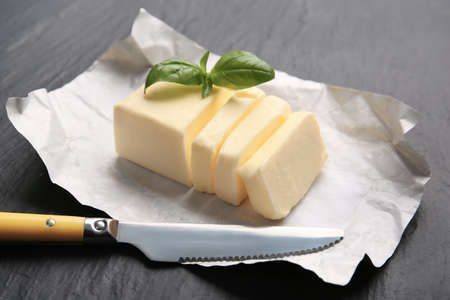 Piece of unwrapped sliced butter, knife and basil leaves on dark table