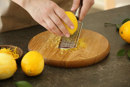 Woman grating zest of lemon on kitchen table Stock Photo