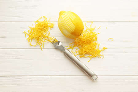 Fresh peeled lemon, special tool and zest on wooden table Stock Photo