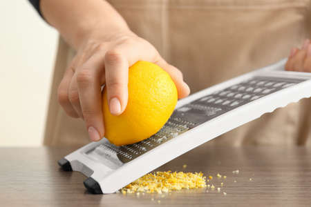 Female chef grating zest of lemon on kitchen table