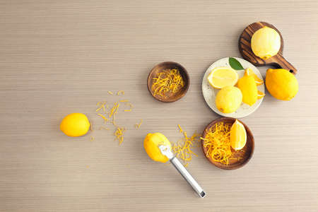 Composition with fresh lemons and zest on wooden table