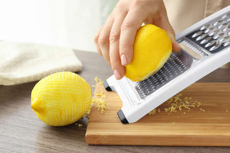 Female chef grating zest of lemon, closeup