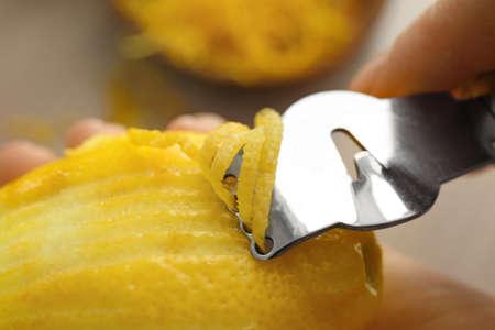 Woman taking off lemon peel with zester, closeup Stock Photo