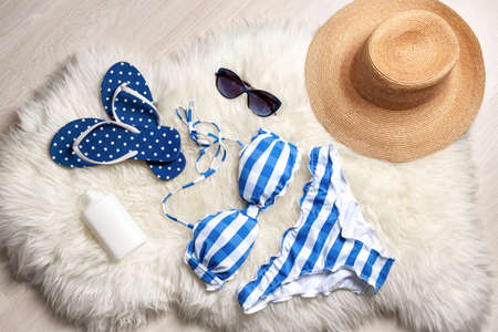 Beautiful swimsuit and different accessories on furry rug