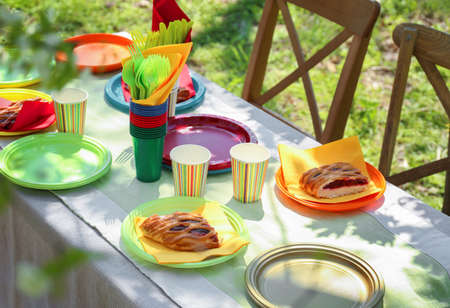 Table served with disposable tableware in garden Stock Photo