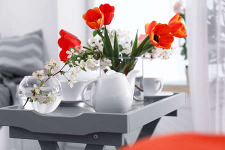 Vase with beautiful flowers and tea set on table in modern veranda interior Stock Photo