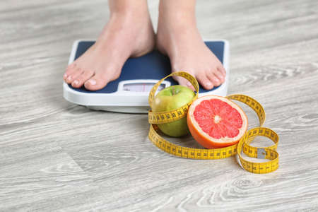 Woman standing on scales near fruits and measuring tape on wooden floor. Concept of weight loss 스톡 콘텐츠