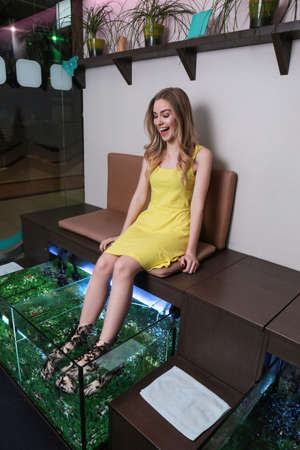 Young woman in beauty salon. Fish pedicure as new modern spa treatment Stockfoto - 98043133