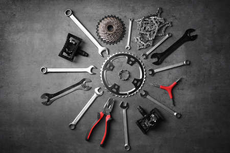 Bicycle parts and repair tools on gray background Stock Photo