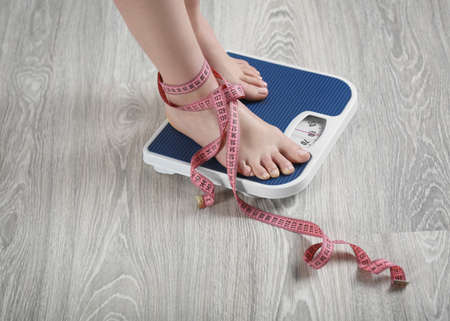 Woman standing on scales with measuring tape on wooden floor. Concept of weight loss