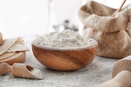 Bowl of wheat flour on blurred background