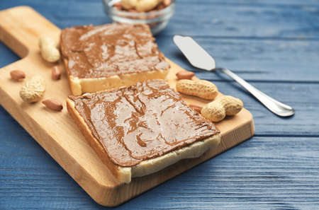Toasts with delicious peanut butter and nuts on wooden table Stock Photo