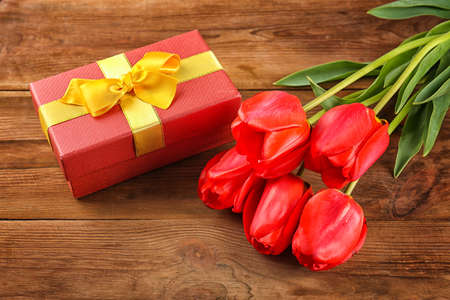 Bouquet of beautiful flowers and giftbox on wooden background, closeup