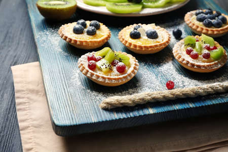 Delicious crispy tarts with berries and custard cream on wooden tray Stock Photo