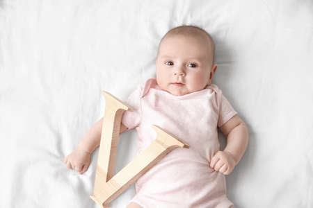 Cute baby with letter V lying on bed. Choosing name concept