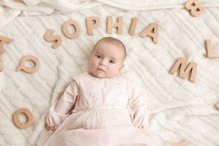 Cute baby with word SOPHIA lying on soft blanket. Choosing name concept