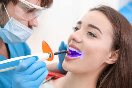 Dentist doing procedure with dental curing UV light in clinic Imagens