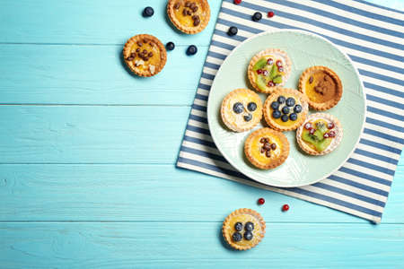 Delicious crispy tarts with berries and custard cream on wooden table