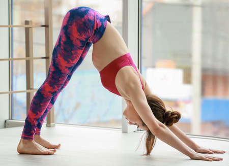 Young woman practicing yoga near big window Stock Photo