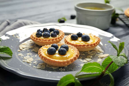 Delicious crispy tarts with blueberries and custard cream on plate Stock Photo
