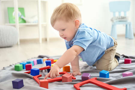 Cute little boy playing on floor at home