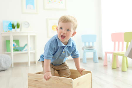 Cute little boy standing in wooden box at home