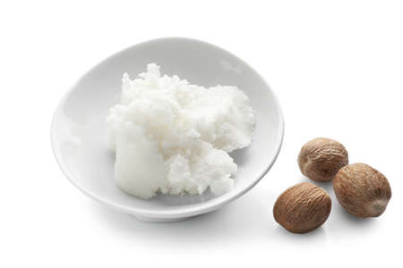 Shea butter in bowl and nuts on white background