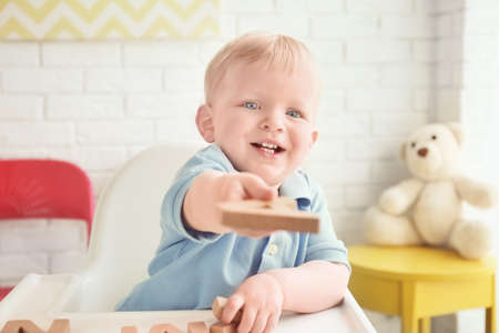 Cute little boy playing with wooden letters while sitting in high chair